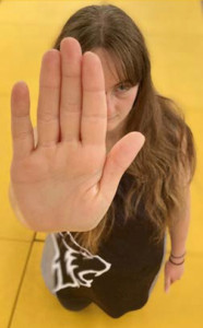 Photo of a woman with her hand held up in a Stop position